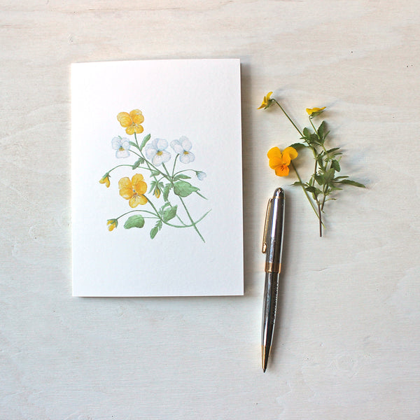Note card featuring a watercolor painting of yellow and white violas. Artist Kathleen Maunder.