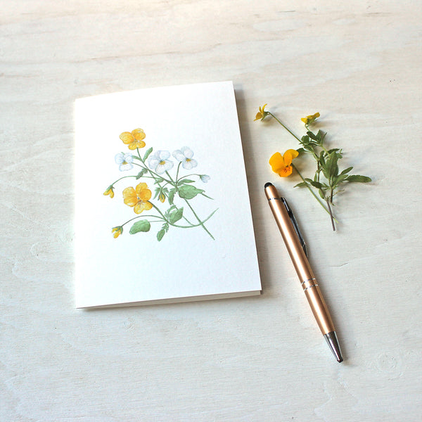 A blank note card featuring a watercolor painting of yellow and white violas.