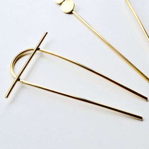 Minimalist hair pin that has a arced top with a 2 inch bar across it resembling the sun on the horizon by Material Wit.