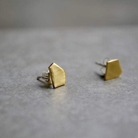 small stud earrings with hand cut angles resembling metal fragments.