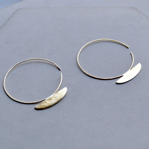 Large brass hoop earrings with a bisected oval shape soldered to the base of the hoop.