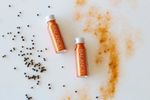 Black pepper fruit, powdered turmeric and Balance the Superfood Shot Turmeric Blend on a table