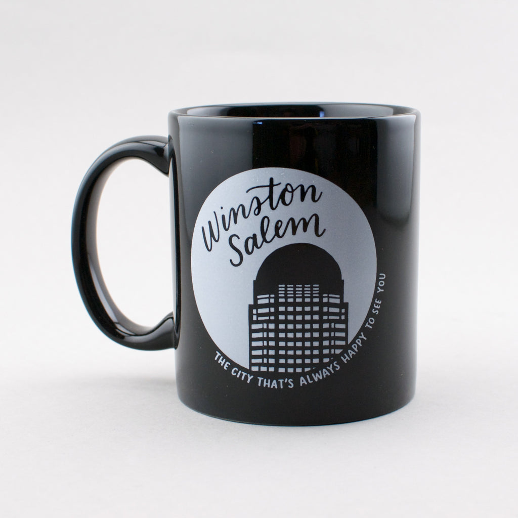 Winston-Salem: the city that's always happy to see you. Black ceramic mug with white print, by Em Dash Paper Co.