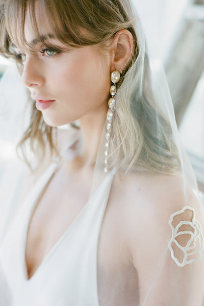 A bride wearing a wedding veil and crystal earrings