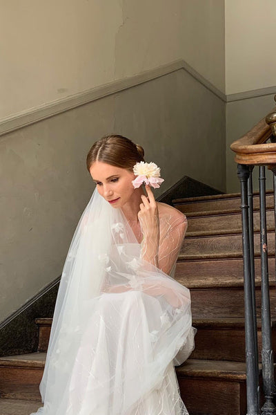 A bride wearing Madame Tulle wedding veil holding a flower