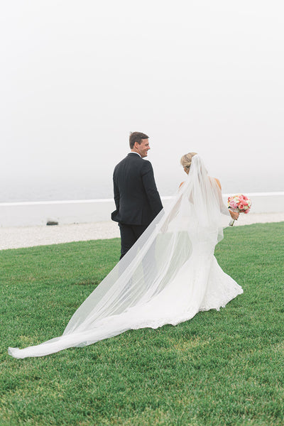 Bride and groom walking together, bride wearing a long cathedral veil
