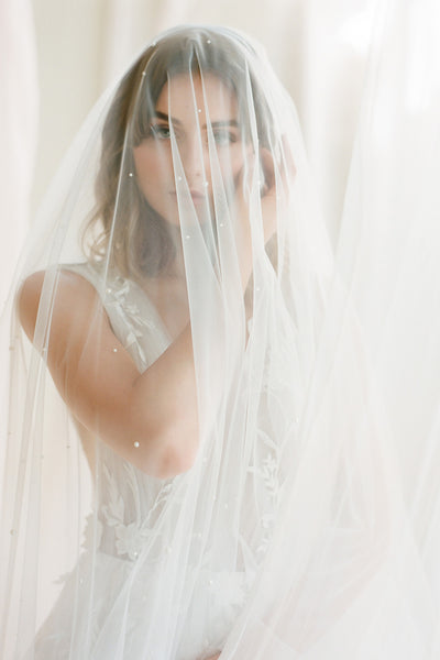 A bride wearing a pearl veil over the face