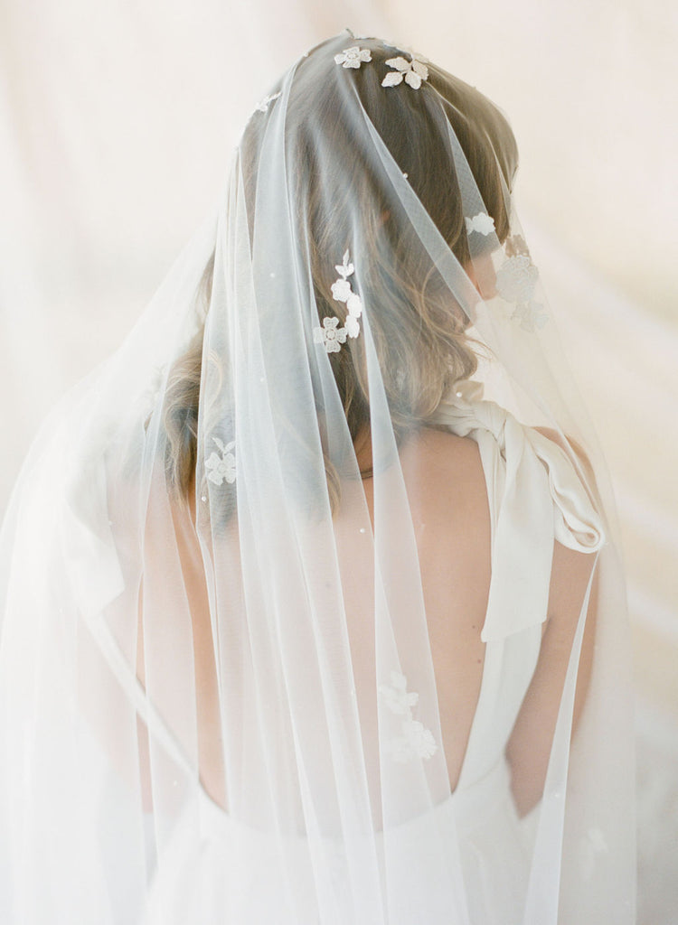 A bride wearing lace wedding veil by Madame Tulle