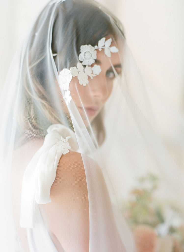 Bride wearing lace wedding veil by Madame Tulle