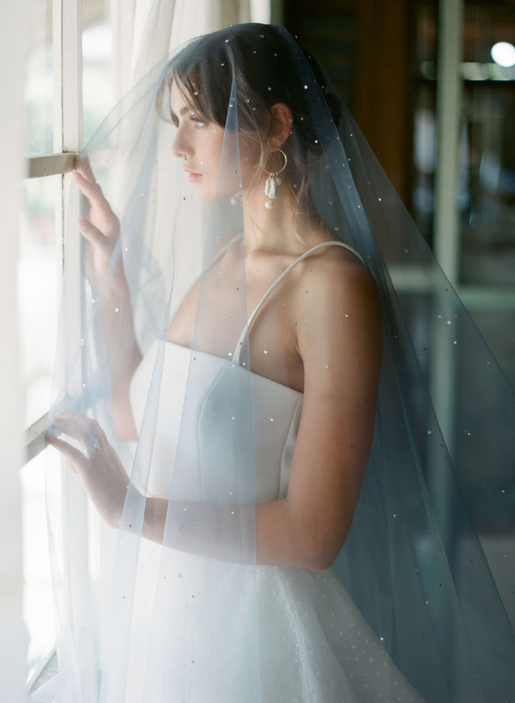 A bride wearing a blue wedding veil with crystals