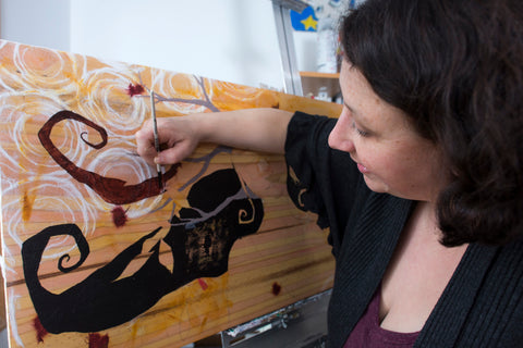 Portland Artist Lea K. Tawd working on her mixed media painting on wood