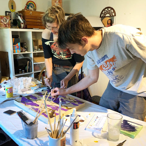 two people painting canvases on a table in an art studio