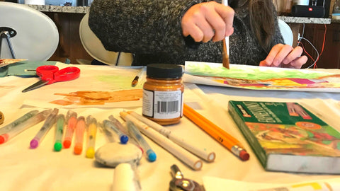 Photograph of a person's hand painting, with art supplies scattered on the table in front of them