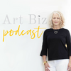 Alyson Stanfield, the art biz coach, wearing a black top and white pants, leaning against a white wall.  Text reads Art Biz Podcast