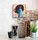 Art print hanging on a brick wall above books, pencils and other items on a desk.  The print by Portland artist Lea K. Tawd portrays a woman and a fox standing in front of a moon and a field of stars.