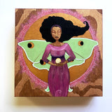 A painting on wood depicting a Black woman with Luna moth wings.  She is wearing a purple dress and has a full golden moon behind her.  She is holding a ball of light in her hand.