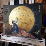 golden moon constellation painting with woman kneeling at a fire. Painting is on an easel and shown at an angle in order to show the gold of the moon.