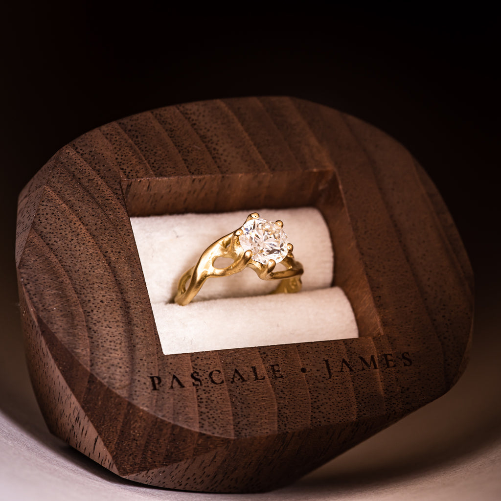 18ct fairtrade yellow gold and diamond ring sat within a dark wood walnut wooden jewellery box