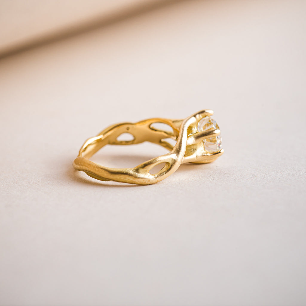 Etwined 18ct yellow gold ring with a branch like design that weaves around a brillliant round diamond