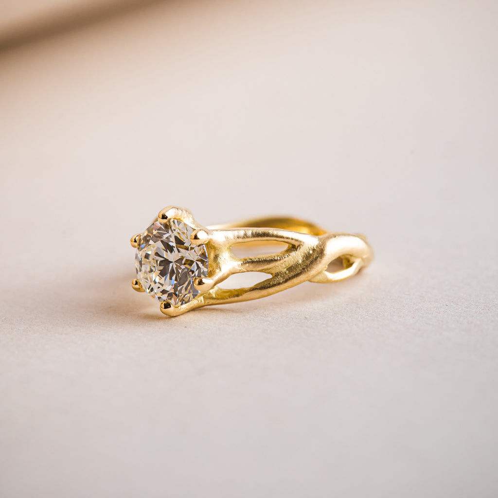 Canadian brilliant round diamond set within a natural, organic weaving 18ct yellow gold ring.