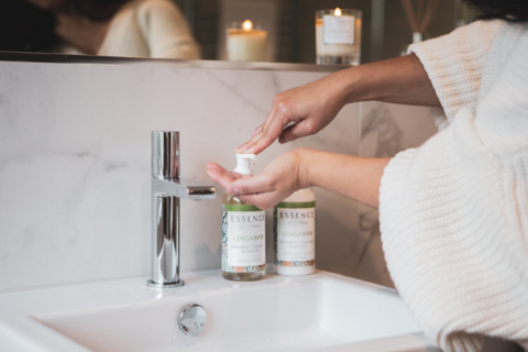 Essence of Harris hand and body lotion being pumped onto hands in a bathroom scene