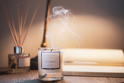 Essence of Harris Seilebost candle placed on a desk with reed diffuser and note book in the background