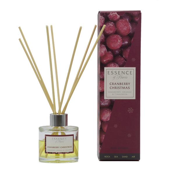 Clear glass reed diffuser with cranberry scented liquid with natural reeds packaged in our Essence of Harris Cranberry Christmas diffuser box