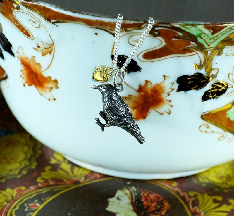Dark silver raven necklace with a bright silver chain and gold vermeil tiny heart
