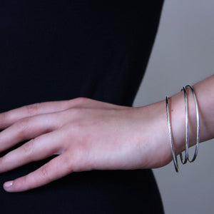 Fine sterling silver bangles on body image