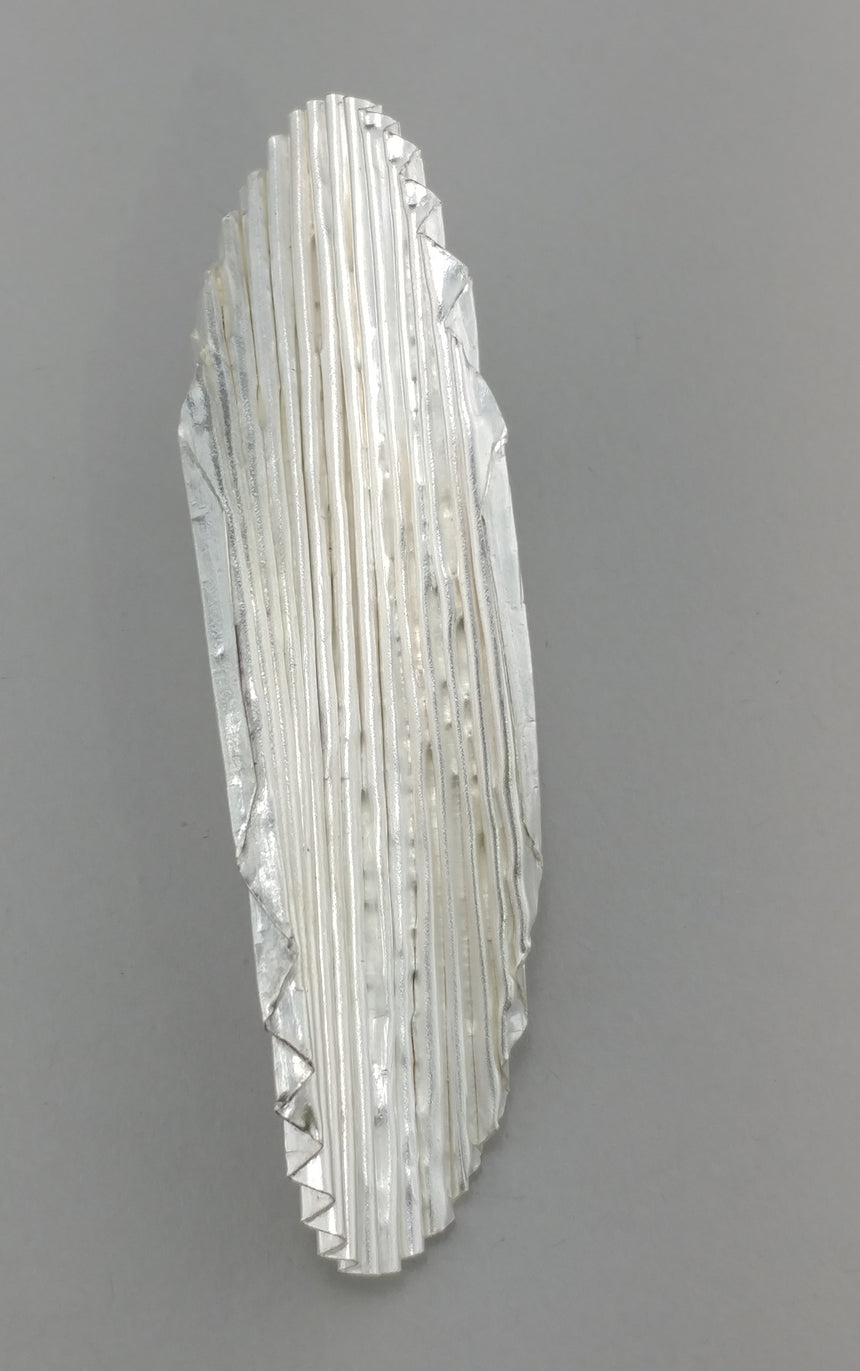 A chip shaped brooch made in fine silver is finely corrugated into tiny pleats.  A single pin on the back has a strong clasp for this statement brooch.