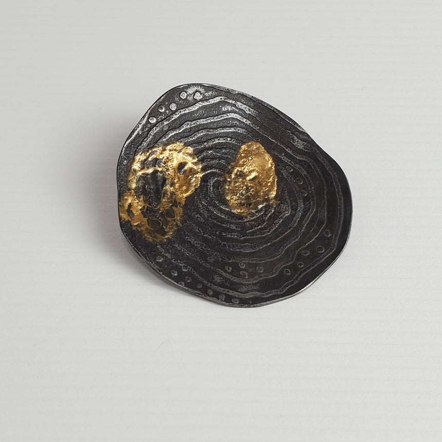 Roundish steel with slightly etched lines and dots that have been patinaed black.  On top of this 24 karat gold has been fused with the steel.  Because this is done with heat, there is little control over how the gold webs and melts in splotches over the steel.  There is a silver tube which can be added to the pin back and then a cord, chain or neckwire can be threaded through the tube to wear as a pendant.