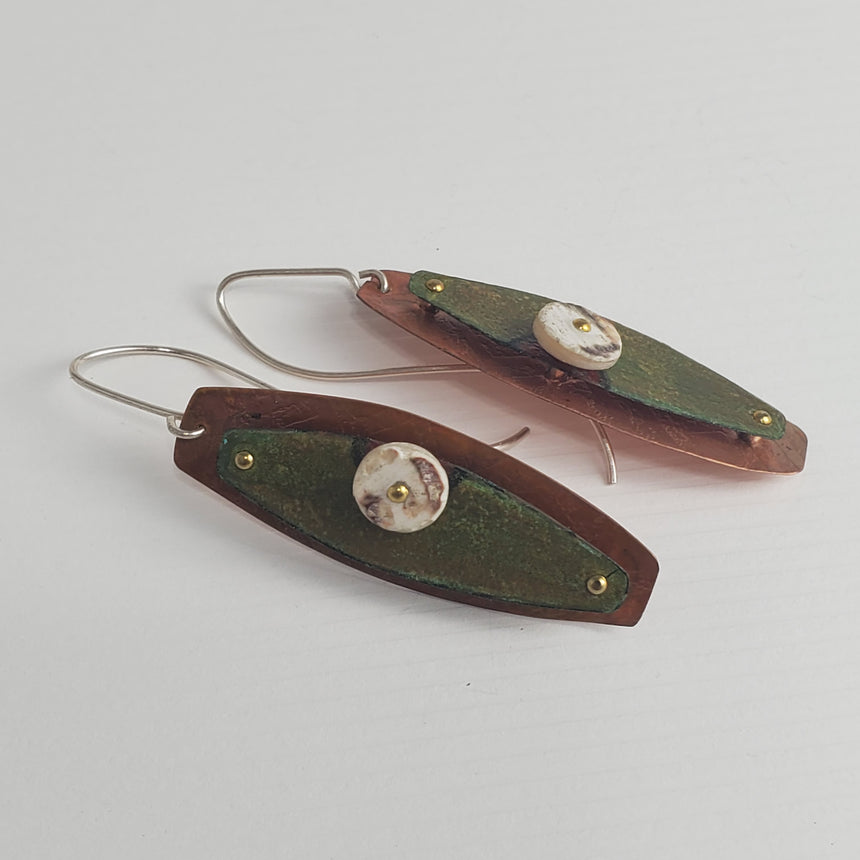 Many layers of khaki green Prisma colored crayon are applied to copper which is then riveted to a textured copper sheet.  There is an accent of a handmade ostrich egg shell bead.