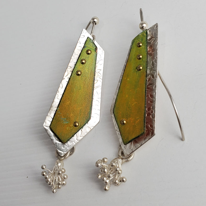 Yellow  and green organic colored Prisma colored pencil on copper is riveted to a floral textured sterling silver base with brass studs.  A sterling silver charm is attached to the bottom of each earring making these truly kinetic.