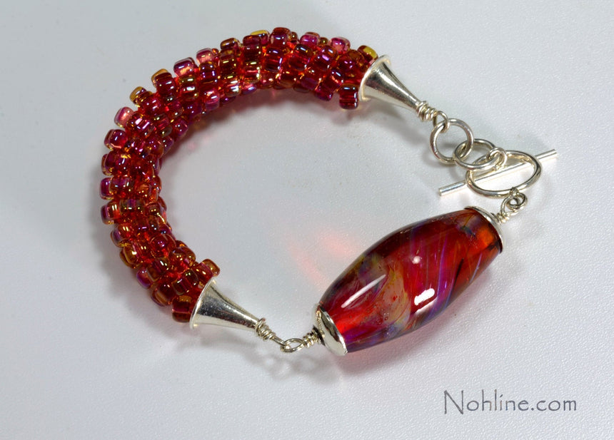 Bright Pink, gold filled beads woven into a kumihimo braid on this bracelet and accented with an oval bright pink handmade lampwork bead with silver caps, and cones. jump rings and clasp.