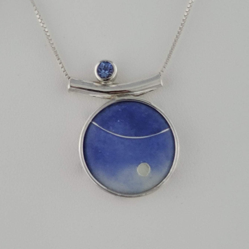 Twilight purple blue has a focal clear circle and a stripe of fine silver wire.  Accented with a 4 mm Tanzanite Stone to one side and a sterling silver box chain.