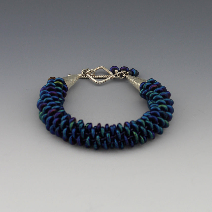 This lovely peacock colored bracelet is made up of off center Czech lentil beads which are woven in a kumihimo braid. Kumihimo is a Japanese weave of 8 different strands on a marudai. The ends are capped with hammered sterling silver cones and a  square twisted wire clasp. Tiny sapphire beads are used to create a dangle.
