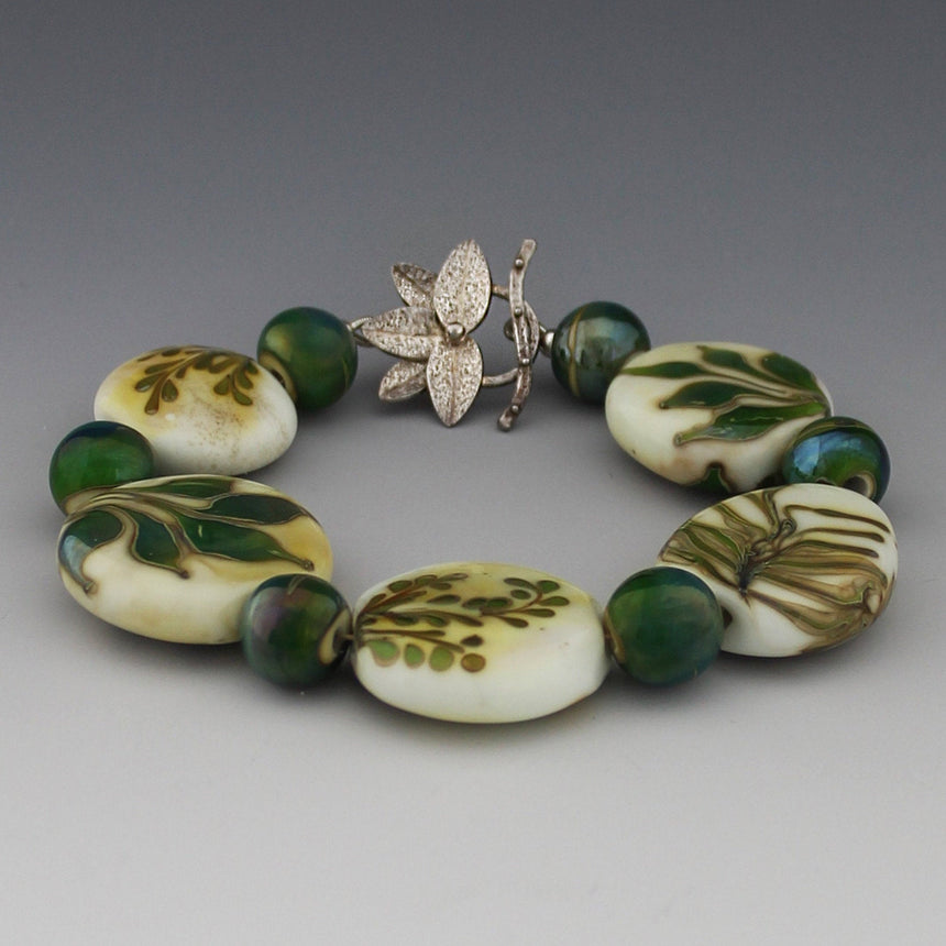 "Five organic lentil beads in ivory colored glass have the design of leaves on them.  These leaves are inspired by my garden and reflect the fine leafed ferns, palms and broad leafed ginger.  the green glass has a special silver reaction so that is shimmers in blue and gold.  The clasp has five leaves with an ""s"" catch."