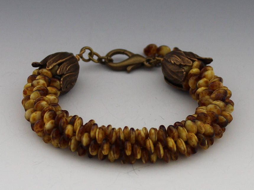 This lovely bracelet is made up of off center Czech lentil beads in tortoise shell colors of brown and gold; which are woven in a kumihimo braid.  Kumihimo is a Japanese weave of 8 different strands on a marudai.  The ends are capped with bronze  acanthus cones and a bronze lobster clasp.  Tiny tiger eye beads are used to create a dangle.