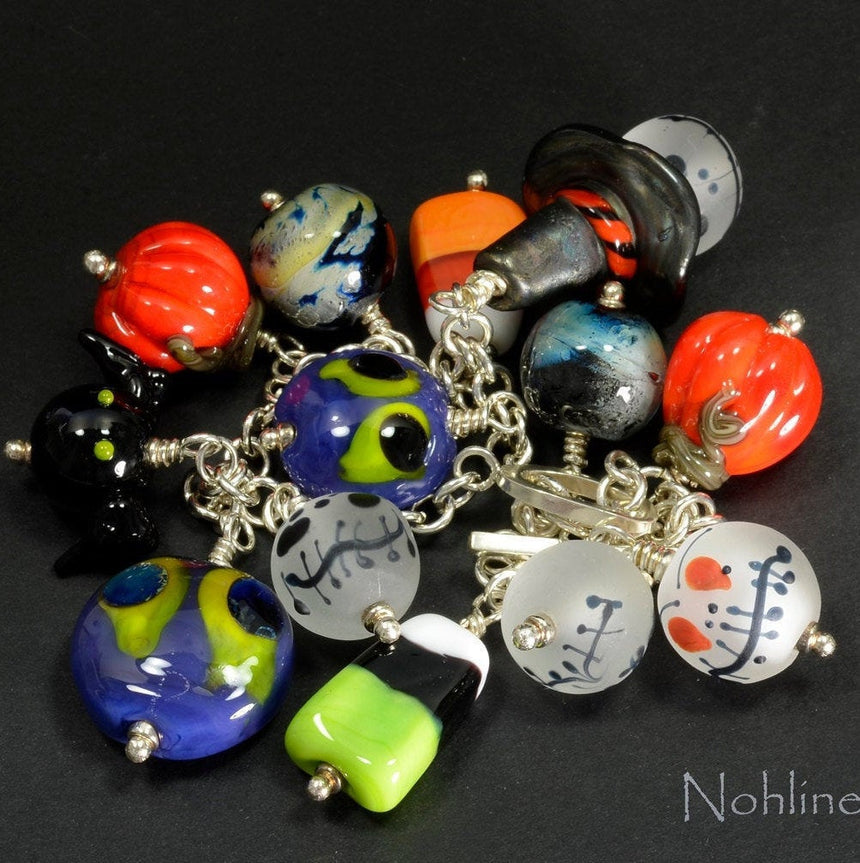 A bracelet of handmade glass beads - purple with lime green and blue eye ghoul;  etched  white jack-o-latterns; orange pumpkins, black bats;  ghoul with a witches hat and swirly skies; all attached to a sterling silver chain bracelet.  Truly a unique piece.