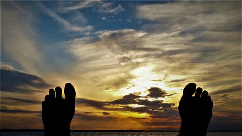 A silhouette of bare feet stretching their toes toward a colorful sunset.