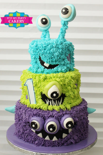 Cute fuzzy monsters stacked tiered first birthday cake