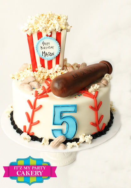 Baseball stitches make the cake look like a baseball.  We add a little slugger bat.  Chocolate shaped peanuts with a little basket of popcorn add to the overall baseball theme.