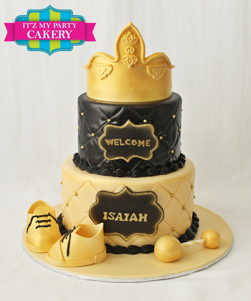 Sugar Crown on a black and gold color scheme baby shower cake with gold baby shoes and a gold rattle