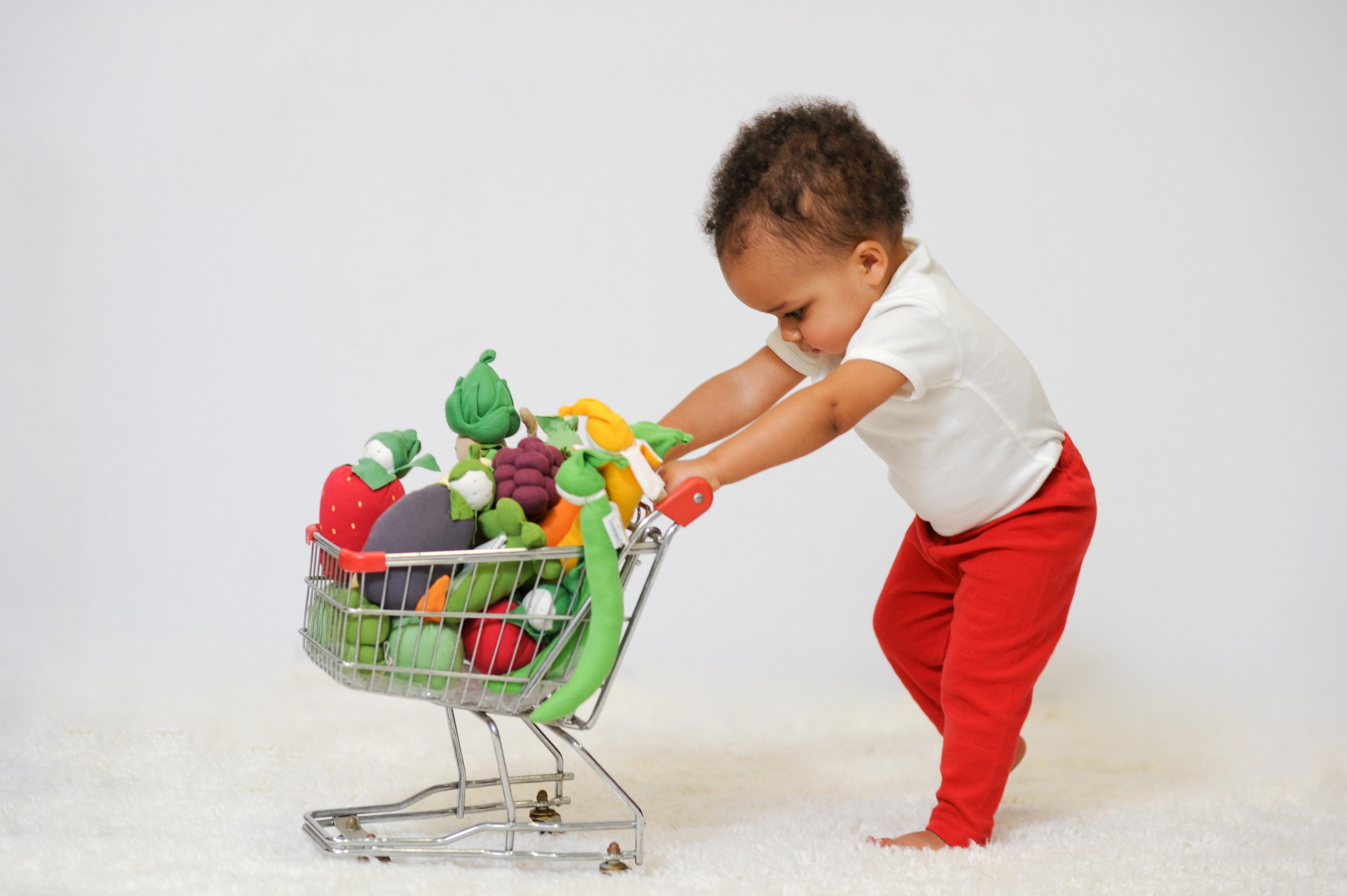 Baby pushing cart full of Fruit and Veggie Toys