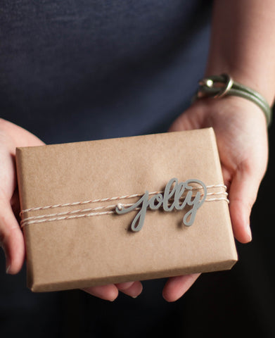a holiday present with a calligraphy gift tag being given