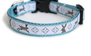 Bunny Trail Dog Collar with light blue webbing and white trim with grayish-brown bunnies and cross emblems