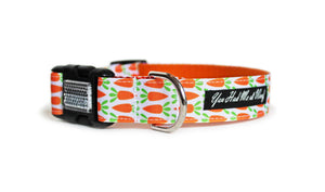 The Carrot Patch Dog Collar with orange webbing and white trim with orange carrots in rows that continue across the length of the collar.