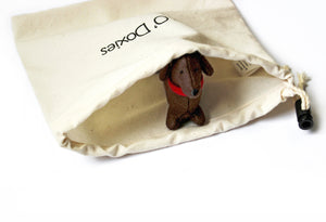 One cute, brown, felt dachshund peeking out of a cream-colored drawstring bag