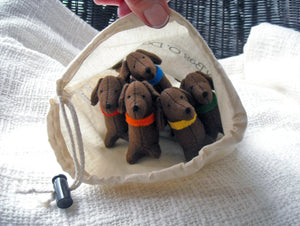 Five cute, brown, felt dachshunds, nestled in a cream-colored drawstring bag