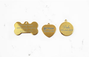 Engraved Gold Dog ID Tag with mirror finish in bone, heart and round shapes on a white marble background